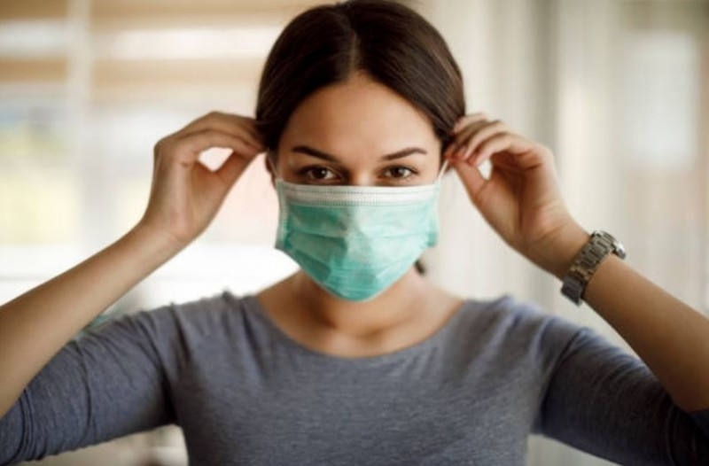 woman putting on non-medical mask